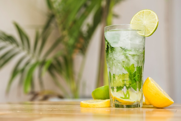 Slices of fruits near glass of drink with ice and herbs on board Free Photo