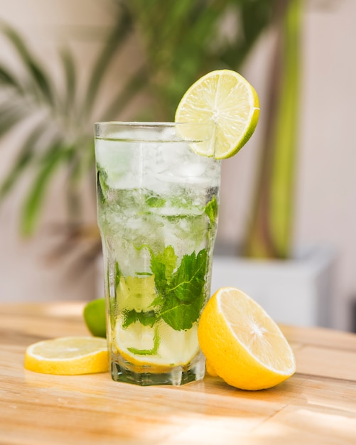 Slices of fruits near glass of drink with ice and herbs on table Free Photo