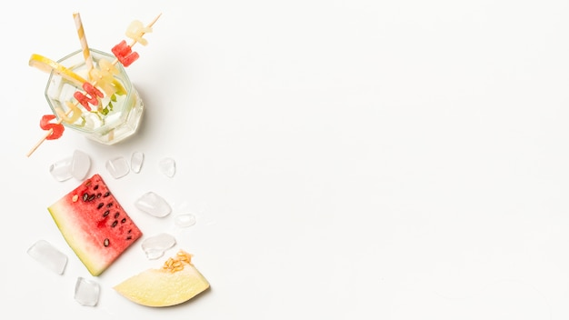 Slices of fruits near ice and summer title on glass with straw Free Photo