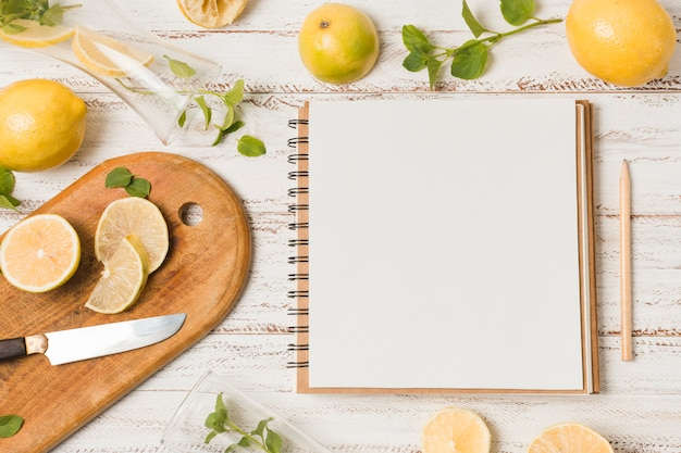 Slices of fruits near knife between herbs and notebook Premium Photo