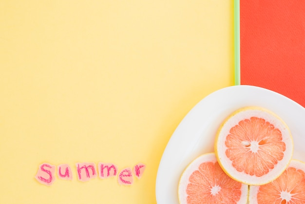 Slices of fruits on plate near summer word Free Photo