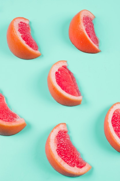 Slices of grapefruits on mint background Free Photo