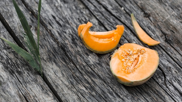 Slices and halved of musk melon on an old wooden backdrop Free Photo