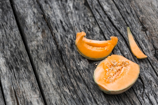 Slices and halved of musk melon on an old wooden table Free Photo