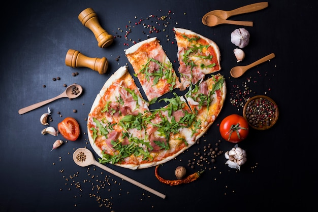 Slices italian pizza with utensils and ingredients over black kitchen worktop Free Photo