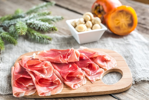 Slices of jamon on the wooden board Premium Photo
