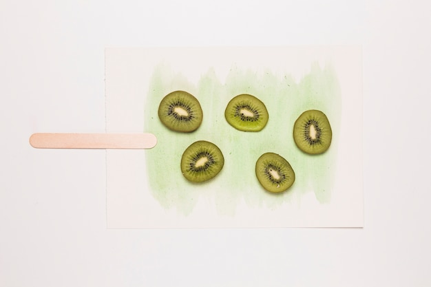 Slices kiwi fruit on watercolor painted in shape of ice cream Free Photo