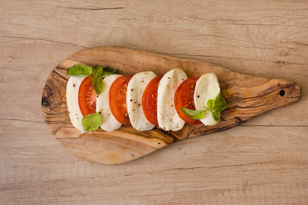 Slices of mozzarella cheese; tomatoes with herb on chopping board against wooden backdrop Free Photo