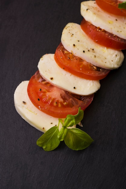 Slices of mozzarella cheese and tomatoes with pepper seasoning and herbs on black background Free Photo