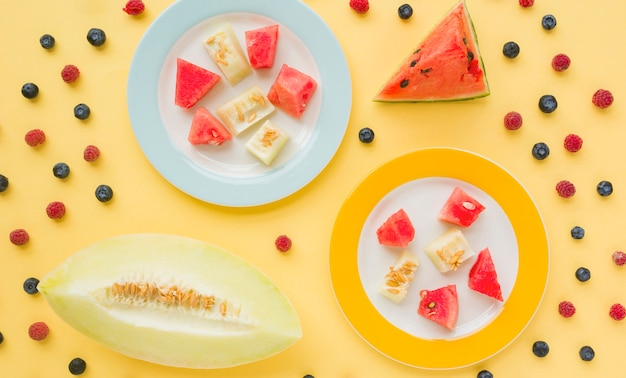 Slices of muskmelon and watermelon on two plated decorated with blueberries and raspberries against yellow background Free Photo