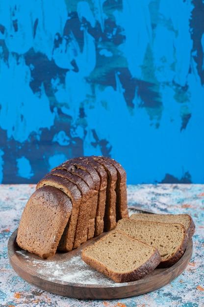 木製の丸いボードに小麦粉と茶色のパンのスライス。 無料写真