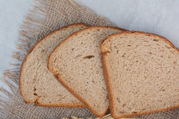 大理石の背景に焼きたての茶色のパンのスライス。 無料写真