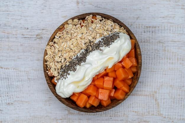 Ломтики спелых сладких плодов папайи с овсяными хлопьями, семенами чиа и белым йогуртом на кокосовой миске Premium Фотографии