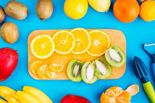 Slices of oranges and kiwi on chopping board surrounded with fruits on blue background Free Photo