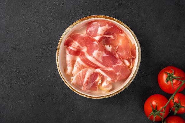 Slices of prosciutto ham in a white ceramic bowl on dark background, next to a branch of cherry Premium Photo