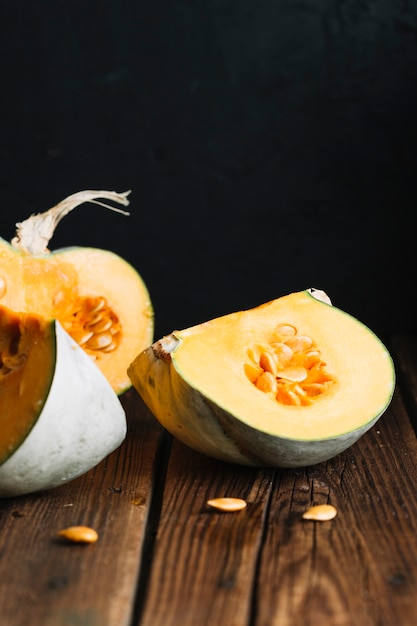 Slices of pumpkin with seeds on wooden background Free Photo