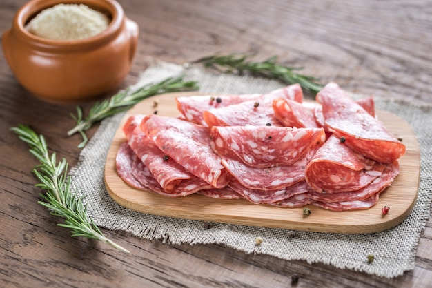 Slices of salami on the wooden board Premium Photo