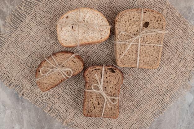 Fette di pane vario legate con una corda sulla superficie in marmo. foto di alta qualità Foto Gratuite