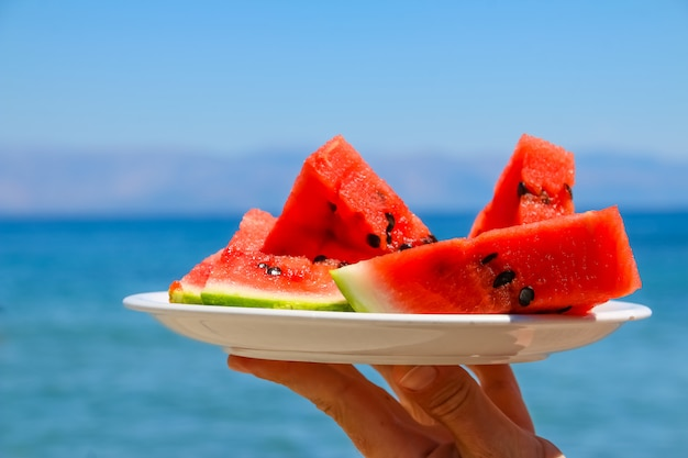Slices of watermelon on the plate on blue sea background.fresh fruit on beach. Premium Photo