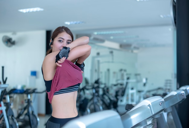 Slide view of fitness woman exercising with running on treadmill machine in gym. Premium Photo