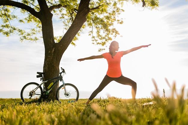 Стройный силуэт красивой женщины занимается спортом утром в парке, занимаясь йогой Бесплатные Фотографии