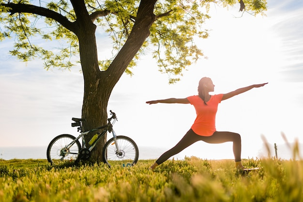 Slim beautiful woman silhouette doing sports in morning in park doing yoga Free Photo