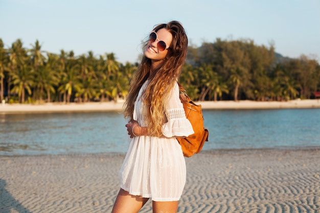Slim beautiful woman in white dress on tropical beach on sunset holding leather backpack. Free Photo