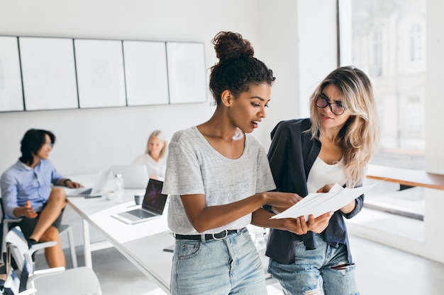 Slim black woman in jeans explaining something to european female colleauge while asian man talking with fair-haired young lady. portrait of managers of international company solving work problems. Free Photo