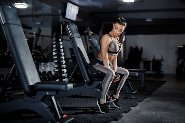 Slim, bodybuilder girl, lifts heavy dumbbell standing in front of the mirror while training in the gym. sports concept, fat burning and a healthy lifestyle Premium Photo