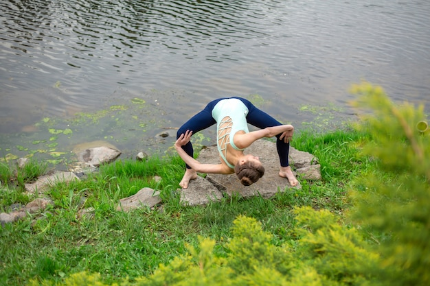 Slim brunette girl doing yoga in the summer on a green lawn by the lake Premium Photo