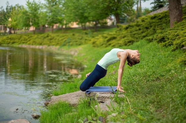 Slim brunette girl doing yoga in the summer on a green lawn Premium Photo