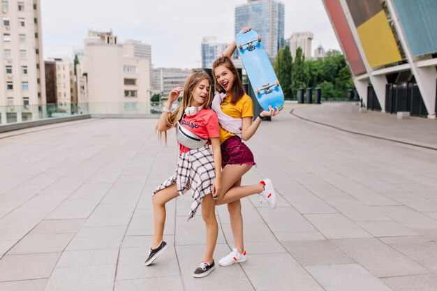 Стройные беззаботные девушки весело танцуют на площади, наслаждаясь летними выходными и хорошей погодой Бесплатные Фотографии