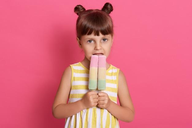 スリムな白人の女の子の子供は彼女の幸せな目で2つの大きなアイスクリームのルックスを保持し、面白い結び目を持っている、ピンクの壁に孤立したポーズ、女性の子供がおいしいアイスクリームをかむ。 無料写真