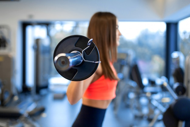 Slim handsome young woman in sportswear squats with a barbell on the shoulder in the gym Premium Photo