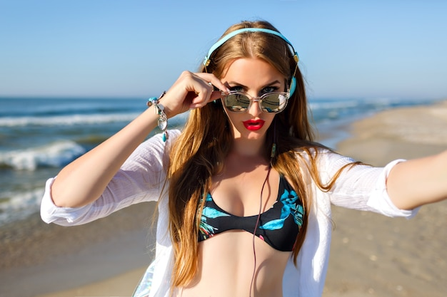 海のリゾートで休んでいる間、セルフィーを作る淡い肌のスリムな長い髪の少女。音楽を聴くと週末に海のそよ風を楽しんでいるサングラスで幸せな女性の屋外のポートレート。 無料写真