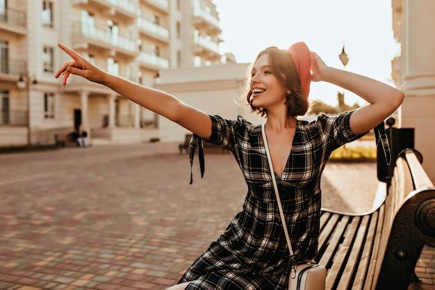 Slim ragazza romantica seduta sulla panchina con il sorriso. colpo esterno di estatico modello femminile francese che punta il dito contro qualcosa. Foto Gratuite
