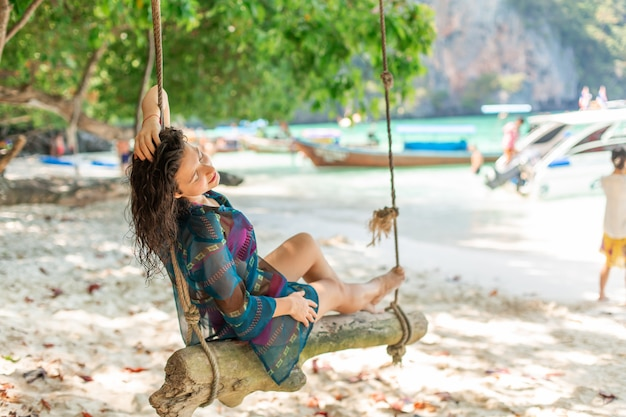 Slim sexy girl model in a swimsuit posing on a wooden swing tied to a tree. on the  of the beach of a tropical island. Premium Photo