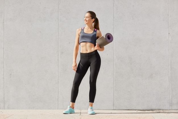 Slim sporty woman holding yoga mat before or after fitness class, stands wearing sportsuit and looking aside Premium Photo