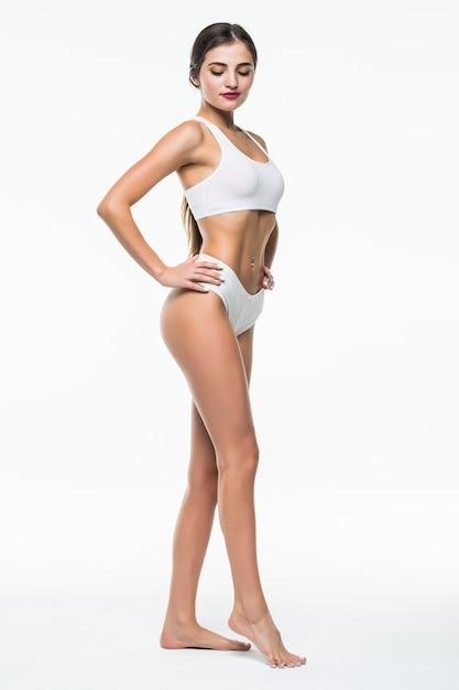 Тонкая загорелая девушка в белом белье позирует изолированные на белой стене. концепция красоты и ухода за телом Бесплатные Фотографии