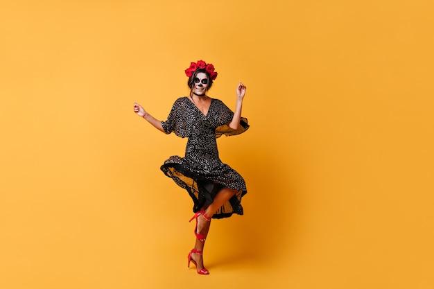 주황색 벽으로 꽃 점프와 춤의 왕관과 함께 슬림 그을린 멕시코 여성 무료 사진