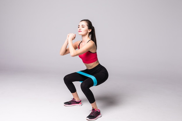 Slim woman doing squats with fitness elastic loop band isolated on white wall Free Photo