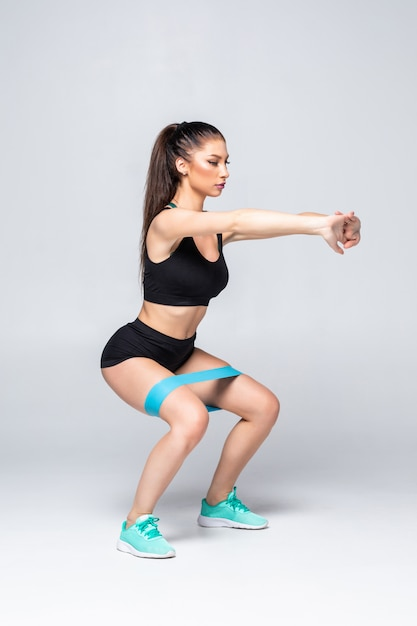 Slim woman doing squats with fitness loop band isolated Free Photo