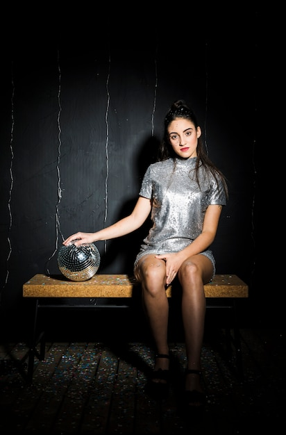 Slim woman in dress with disco ball on bench Free Photo