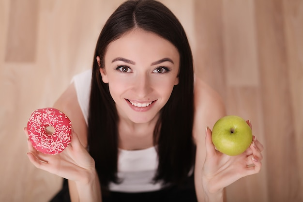 Slim woman hold in hand pink donut and green apple Premium Photo