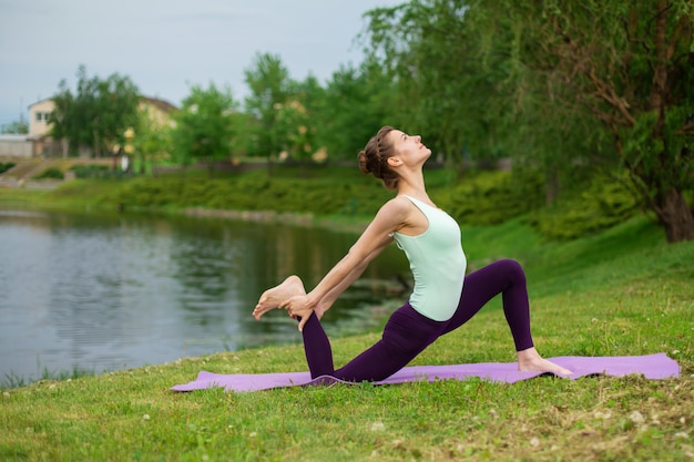 Slim young brunette yogi performs no complicated yoga exercises on the green grass in summer against the  of nature Premium Photo