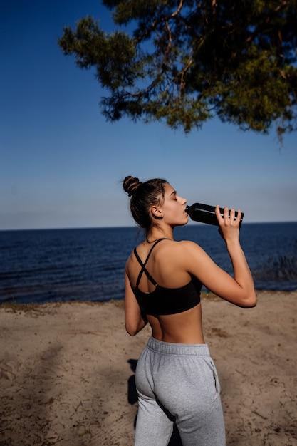 Тонкая молодая женщина питьевой воды после тренировки Бесплатные Фотографии