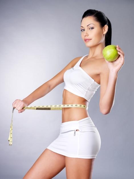 Худеющая женщина измеряет фигуру сантиметровой лентой и держит в руках яблоко. кокнепт здорового образа жизни. Бесплатные Фотографии