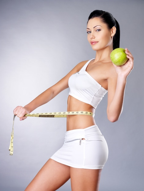 Slimming woman measures figure with a measuring tape and holding the apple. healthy lifestyle cocnept. Free Photo