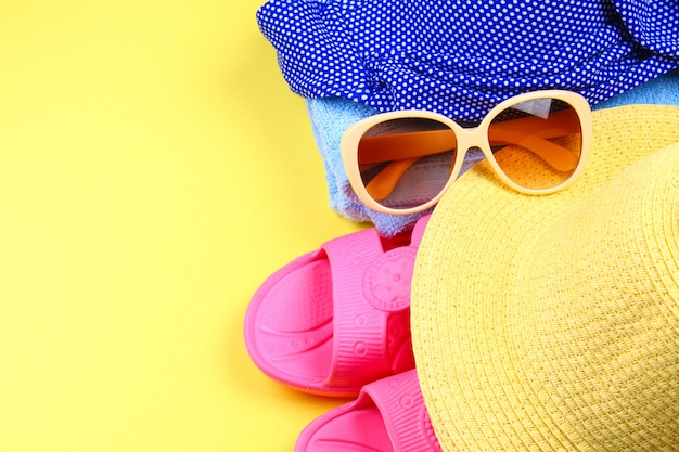 Slippers, swimsuit bikini, towel, hat and sunglasses on a pastel yellow background. Premium Photo