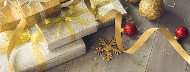 나무 테이블 배너 배경에 은색과 금색 쉬머 크리스마스 선물 상자 프리미엄 사진